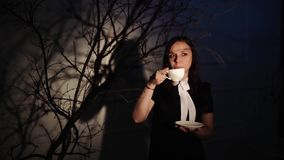 Woman with cup of coffee in dark place. Young dreamy woman enjoying coffee while standing in ray of light beside. Young dreamy woman enjoying coffee while stock video