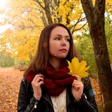 Young dreamy woman is holding a yellow maple leaf. Autumn park is in the background stock images