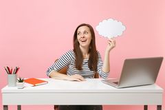 Young dreamy woman looking up holding empty blank Say cloud speech bubble sit and work at white desk with pc laptop. Isolated on pastel pink background stock photography