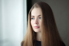 Young dreamy woman near window at home, closeup up natural light portrait. Young dreamy woman near window at home, closeup up natural light Royalty Free Stock Photos