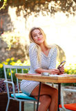 Young dreamy woman sits at table of summer cafe Stock Photos