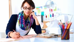 Young dressmaker designing clothes pattern on paper.  royalty free stock image