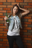 Young drinking girl. Teenage girl holding a green bottle of beer against a brick wall Stock Photography