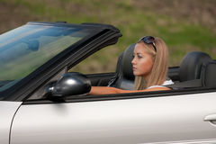 Young driver. Young girl driving cabrio car, on sunset light Royalty Free Stock Photo