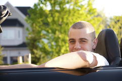 Young driver. Male young driver smiling while sitting in a convertible Royalty Free Stock Photo