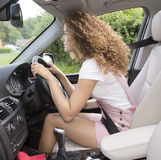 Young driver with a bad posture for driving. Young female driver with a bad posture and bad driving position. Female motorist Royalty Free Stock Photos