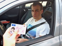 Young Driver In The Car Inspected By Police. Man sitting in the car and being stopped by police and showing his driving licence Stock Photo