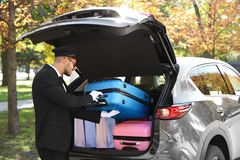 Young driver loading suitcases into car trunk. Outdoors stock photo