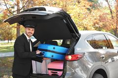 Young driver loading suitcases into car trunk. Outdoors stock photography
