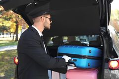 Young driver loading suitcases into car trunk stock photo