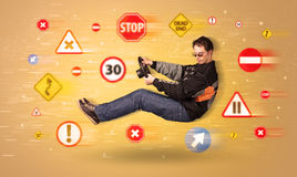 Young driver with road signs around him Stock Photos