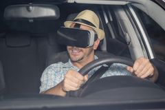 Man learning to drive with virtual reality glasses. Young driver sitting in car and using virtual reality glasses simulation app Royalty Free Stock Photography