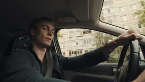 Young driver talks to passenger while riding car through city street. Young caucasian driver talks to passenger and change radio stations while riding car stock footage
