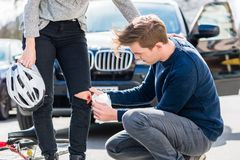 Young driver using a sterile bandage from his first aid kit. Young male driver using a sterile adhesive bandage from his first aid kit to help an injured female Royalty Free Stock Photos