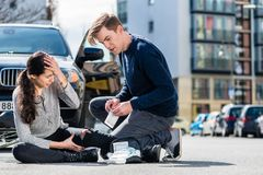 Young driver using a sterile bandage from his first aid kit to h. Young male driver using a sterile adhesive bandage from his first aid kit to help an injured Stock Photography