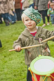 Young Drummer at Braemar Gathering. Portrait of small boy playing his drum alongside the massed  pipes and drums and entertaining the crowds with his enthusiasm Stock Images
