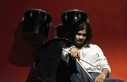 Young drummer holding sticks and sitting next to drum kit Stock Photography