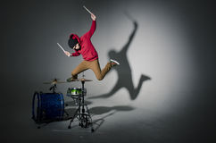Young drummer jumping while playing. In studio royalty free stock image