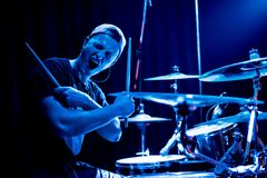Drummer at the concert. Young drummer posing in front of the camera in a blue concert light royalty free stock photos