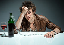Young drunk man with a bottle of red wine Royalty Free Stock Photos