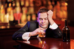 Young drunk man drinking Stock Images