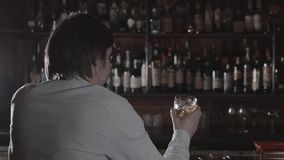 Young drunk man drinking alcohol in the bar alone. Lonely businessman with whiskey in bar at night. Loneliness concept. stock video footage