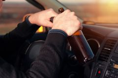 Young drunk man driving a car and drinking beer Stock Images