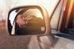 Young drunk man driving a car and drinking beer Stock Photos