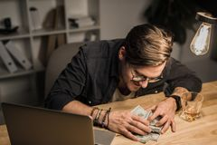 Drunk man with heap of cash. Young drunk man with heap of cash at workplace Stock Images
