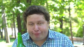 Young drunk man holding a beer bottle and making funny faces outdoor in green park stock video footage