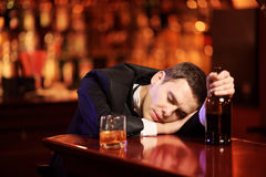 Young drunk man sleeping in the bar. With glass of whiskey in his hand Stock Image