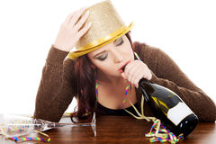 Young drunk woman by a table and with empty bottle. Royalty Free Stock Photos