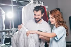 young dry cleaning workers scanning barcode on bag stock photo