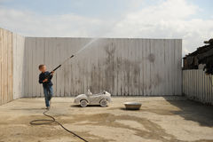A young dude plays with a car wash hose. And a race prize in a rural compound in a hot summer stock photos
