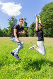 Young dutch couple jumping in green meadow Royalty Free Stock Images