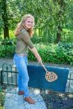 Young dutch woman beating door mat with carpet beater stock photos