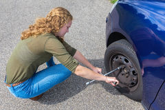 Young dutch woman changing car tire on road Stock Image