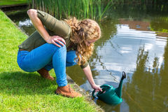 Young dutch woman filling green caster with water. Young caucasian woman filling green caster with water in pond royalty free stock photography
