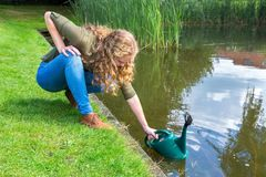 Young european woman filling caster with water. Young dutch woman filling green caster with water in nature royalty free stock photos