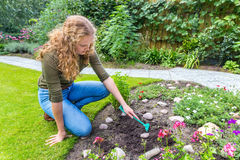 Young dutch woman raking in garden royalty free stock photography