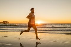 Young dynamic athlete runner man with fit strong body training on Summer sunset beach running barefoot in sport healthy and fitne stock photography