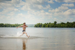 Young dynamic man runs in water Royalty Free Stock Photography