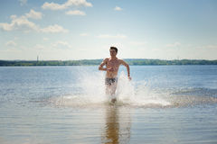 Young dynamic man runs in water Stock Photography