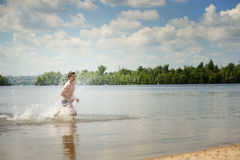 Young dynamic man runs in water Stock Photo