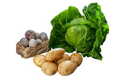 Young early harvest potato, garlic in a basket and fresh young cabbage isolated on white background Royalty Free Stock Images