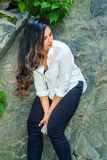 Young East Indian American Woman with long hair traveling, relaxing at Central Park, New York City. Wearing white long sleeve shirt, black pants, standing stock photos