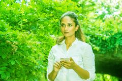 Young East Indian American Woman texting on cell phone outdoor at Central Park, New York. Wearing white shirt, standing in front of street bridge with green royalty free stock photography