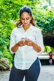 Young East Indian American Woman texting on cell phone outdoor at Central Park, New York. Wearing white shirt, black pants, standing in front of street bridge stock image