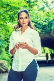 Young East Indian American Woman texting on cell phone outdoor at Central Park, New York. Wearing white shirt, black pants, standing in front of street bridge stock photos