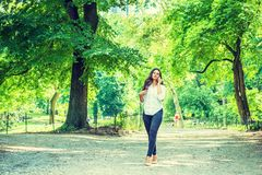 Young East Indian American Woman traveling, relaxing at Central Park, New York. Wearing white shirt, black pants, high heels, walking on road with green trees royalty free stock photography